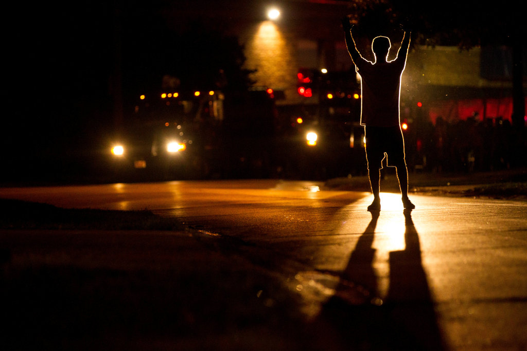 A man raises his arms to police officials during a demonstration after the police shooting of Michael Brown, 18, in Ferguson (Whitney Curtis for The New York Times)