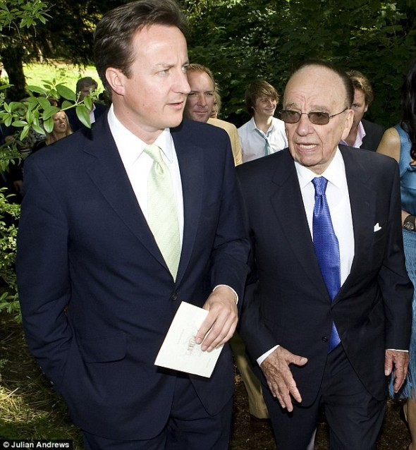 David Cameron talking to Rupert Murdoch at the wedding of Rebecca Wade, former C.E.O of News International, a Murdoch-owned company.  Image via The Daily Mail.