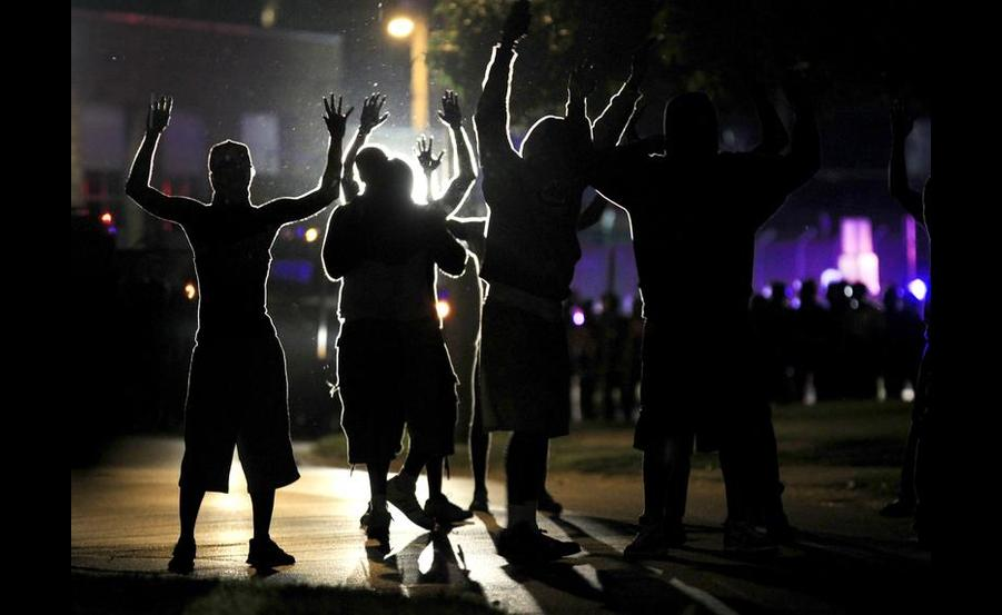 Protestors with their hands up as police wearing riot gear move toward their position in Ferguson, Mo. (AP/Jeff Roberson).