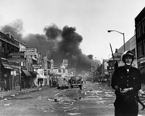 source: PBS.org, a police officer stands guard in a Detroit street on July 25, 1967, as buildings are burning during riots that erupted in Detroit following a police operation. Photo by AFP/Getty Images