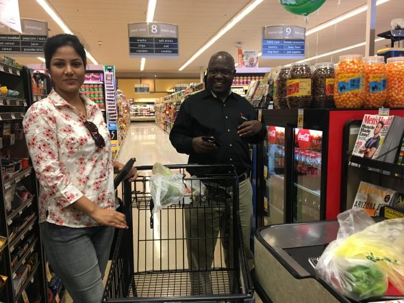 Kazi Mohua, left, and Paul Nyongesa wait in line at Safeway to purchase ingredients. Photo by Tynin Fries.